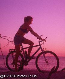 Woman on beach w/ bike at dusk